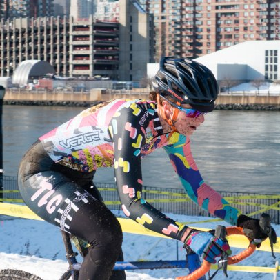 woman races cyclocross in mud, snow, New York City background