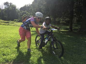 woman helps girl learn to ride bicycle