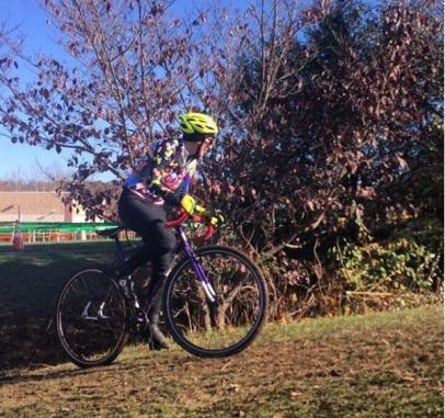 woman races cyclocross, climbing hill