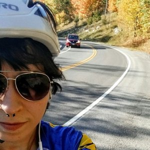 woman over-the-shoulder selfie on a roadside while cycling
