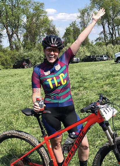 Lauren raises her hand in the air after a mountain bike race.