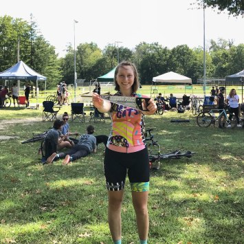 woman holds up sword prize at a bike race